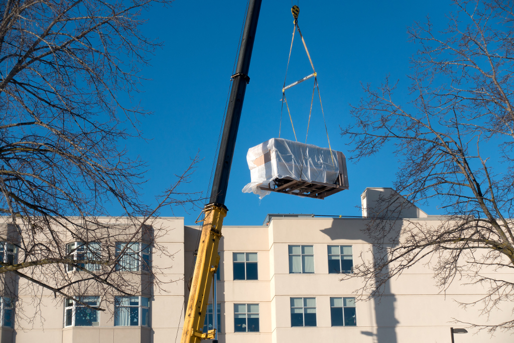 Crane lifting air conditioning unit to top of building
